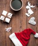 Φλιτζάνι του καφέ και καπέλο Santas, σύνολο Χριστουγέννων, δώρο και χριστουγεννιάτικο δέντρο Εορτασμός Στοκ Φωτογραφία
