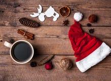 Φλιτζάνι του καφέ και καπέλο Santas, σύνολο Χριστουγέννων, δώρο και χριστουγεννιάτικο δέντρο Εορτασμός Στοκ Φωτογραφίες
