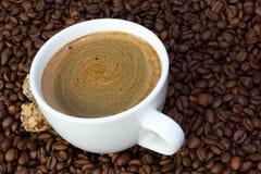 Φλιτζάνι του καφέ και καραμέλες σε ένα υπόβαθρο φασολιών καφέ Στοκ εικόνα με δικαίωμα ελεύθερης χρήσης