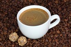Φλιτζάνι του καφέ και καραμέλες σε ένα υπόβαθρο φασολιών καφέ Στοκ Φωτογραφίες