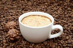 Φλιτζάνι του καφέ και καραμέλες σε ένα υπόβαθρο φασολιών καφέ Στοκ φωτογραφία με δικαίωμα ελεύθερης χρήσης