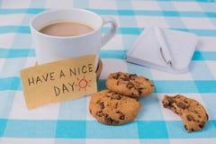 Φλιτζάνι του καφέ και μπισκότα στον πίνακα Επιθυμία μιας συμπαθητικής ημέρας στοκ εικόνα με δικαίωμα ελεύθερης χρήσης