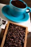 Φλιτζάνι του καφέ και ξύλινα εμπορευματοκιβώτια που γεμίζουν με τα φασόλια cofee Στοκ Εικόνα