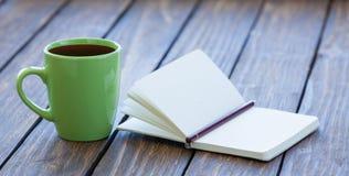 Φλιτζάνι του καφέ και σημειωματάριο με το μολύβι στοκ εικόνες