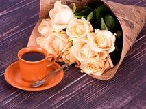 Φλιτζάνι του καφέ και τριαντάφυλλα στο ξύλινο υπόβαθρο στοκ φωτογραφία