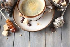 Φλιτζάνι του καφέ, κύβοι ζάχαρης και πτώσεις σοκολάτας στο παλαιό ξύλινο υπόβαθρο με το διάστημα αντιγράφων Στοκ Εικόνες