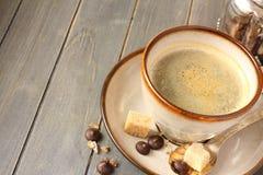 Φλιτζάνι του καφέ, κύβοι ζάχαρης και πτώσεις σοκολάτας στο παλαιό ξύλινο υπόβαθρο με το διάστημα αντιγράφων Στοκ Φωτογραφία