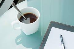 Φλιτζάνι του καφέ με ένα βιβλίο στο γραφείο, έγγραφο Στοκ Εικόνες