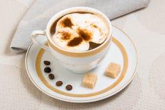 Φλιτζάνι του καφέ με κρέμα και δύο κύβους της καφετιάς ζάχαρης Στοκ εικόνες με δικαίωμα ελεύθερης χρήσης