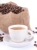 Φλιτζάνι του καφέ με μια burlap τσάντα που γεμίζουν με τα φασόλια καφέ Στοκ Φωτογραφία