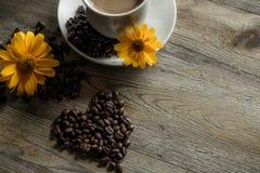 Φλιτζάνι του καφέ με τα κίτρινα λουλούδια στο υπόβαθρο Στοκ Φωτογραφίες