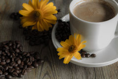 Φλιτζάνι του καφέ με τα κίτρινα λουλούδια στο υπόβαθρο Στοκ εικόνα με δικαίωμα ελεύθερης χρήσης