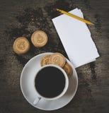 Φλιτζάνι του καφέ με τα μπισκότα και ανοιγμένο σημειωματάριο στο γραφείο Τοπ όψη Στοκ Φωτογραφία