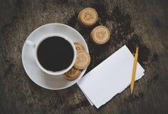 Φλιτζάνι του καφέ με τα μπισκότα και ανοιγμένο σημειωματάριο στο γραφείο Τοπ όψη Στοκ Φωτογραφίες