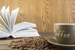 Φλιτζάνι του καφέ με τα φασόλια μπροστά από το ανοικτό βιβλίο που στέκεται σε ένα W Στοκ φωτογραφία με δικαίωμα ελεύθερης χρήσης