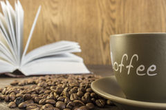 Φλιτζάνι του καφέ με τα φασόλια μπροστά από το ανοικτό βιβλίο Στοκ Εικόνα