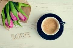 Φλιτζάνι του καφέ με την ανθοδέσμη των ρόδινων τουλιπών και της ξύλινης ΑΓΑΠΗΣ λέξης Στοκ Φωτογραφία
