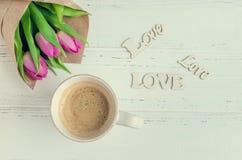 Φλιτζάνι του καφέ με την ανθοδέσμη των ρόδινων τουλιπών και της ξύλινης ΑΓΑΠΗΣ λέξεων Στοκ φωτογραφία με δικαίωμα ελεύθερης χρήσης