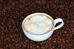 Φλιτζάνι του καφέ με την κρέμα σε ένα υπόβαθρο φασολιών καφέ Στοκ εικόνα με δικαίωμα ελεύθερης χρήσης