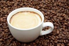 Φλιτζάνι του καφέ με την κρέμα σε ένα υπόβαθρο φασολιών καφέ Στοκ Εικόνες