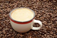 Φλιτζάνι του καφέ με την κρέμα σε ένα υπόβαθρο φασολιών καφέ Στοκ Φωτογραφίες
