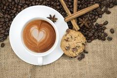 Φλιτζάνι του καφέ με τη μορφή καρδιών στον αφρό hessian στο υπόβαθρο στοκ φωτογραφία με δικαίωμα ελεύθερης χρήσης