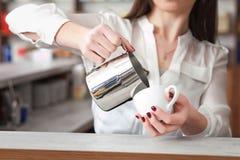 Φλιτζάνι του καφέ με το γάλα στο χέρι γυναικών ` s Στοκ Φωτογραφίες