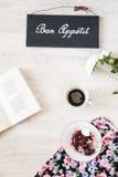 Φλιτζάνι του καφέ με το επιδόρπιο και βιβλίο στον πίνακα Στοκ εικόνα με δικαίωμα ελεύθερης χρήσης