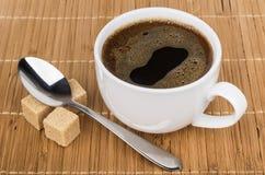 Φλιτζάνι του καφέ με το κουτάλι και ζάχαρη κομματιών στον πίνακα Στοκ Φωτογραφίες