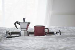 Φλιτζάνι του καφέ με το kattle σε έναν ξύλινο δίσκο στο άσπρο κρεβάτι Στοκ εικόνες με δικαίωμα ελεύθερης χρήσης