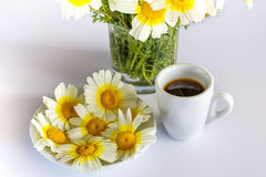 Φλιτζάνι του καφέ, μια ανθοδέσμη των chamomiles και chamomiles σε ένα πιάτο Στοκ Φωτογραφίες
