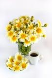 Φλιτζάνι του καφέ, μια ανθοδέσμη των chamomiles και chamomiles σε ένα πιάτο Στοκ Εικόνες