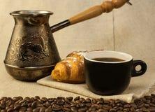 Φλιτζάνι του καφέ, δοχείο καφέ χαλκού Τούρκου και croissants Στοκ Εικόνες