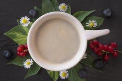 Φλιτζάνι του καφέ πρωινού με τις μαργαρίτες, τα φύλλα, τις κόκκινες σταφίδες και τα βακκίνια Στοκ φωτογραφία με δικαίωμα ελεύθερης χρήσης