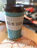 Φλιτζάνι του καφέ σε έναν καφέ με & x22 με κρατήστε closer& x22  μήνυμα στοκ εικόνα