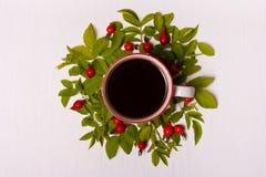 Φλιτζάνι του καφέ σε ένα άσπρο υπόβαθρο στα φύλλα και τα κόκκινα μούρα φ Στοκ Φωτογραφίες