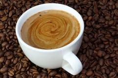 Φλιτζάνι του καφέ σε ένα υπόβαθρο φασολιών καφέ Στοκ φωτογραφία με δικαίωμα ελεύθερης χρήσης