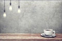 Φλιτζάνι του καφέ στον ξύλινο πίνακα κοντά στο συμπαγή τοίχο Στοκ Εικόνες