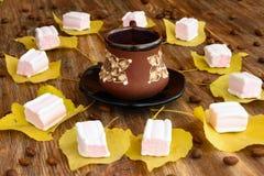 Φλιτζάνι του καφέ στο κέντρο και κίτρινα φύλλα με marshmallows Στοκ εικόνα με δικαίωμα ελεύθερης χρήσης
