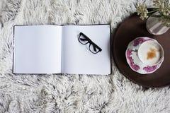 Φλιτζάνι του καφέ στο κρεβάτι με ένα άνετο κάλυμμα στοκ εικόνα