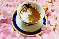 Φλιτζάνι του καφέ στο υπόβαθρο λουλουδιών. Στοκ Φωτογραφίες