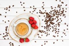 Φλιτζάνι του καφέ, φασόλια καφέ, φράουλες Τοπ όψη Στοκ Εικόνα