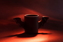 Φλιτζάνι του καφέ ως ρόπαλο για αποκριές στο μαύρο υπόβαθρο ανοικτό κόκκινο σκιά παιχνίδι Έννοια Στοκ εικόνες με δικαίωμα ελεύθερης χρήσης