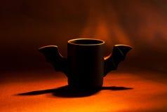 Φλιτζάνι του καφέ ως ρόπαλο για αποκριές στο μαύρο υπόβαθρο ανοικτό κόκκινο σκιά παιχνίδι Έννοια Στοκ Εικόνες