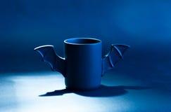 Φλιτζάνι του καφέ ως ρόπαλο για αποκριές στο μαύρο υπόβαθρο Μπλε φως και σκιά παιχνίδι Έννοια Στοκ φωτογραφία με δικαίωμα ελεύθερης χρήσης