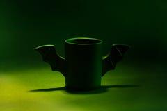 Φλιτζάνι του καφέ ως ρόπαλο για αποκριές στο μαύρο υπόβαθρο Πράσινο φως και σκιά παιχνίδι Έννοια Στοκ Εικόνες