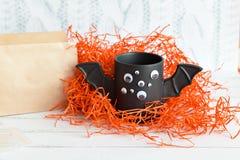 Φλιτζάνι του καφέ όπως ένα ρόπαλο με τα μάτια στο άσπρο υπόβαθρο αποκριών παιχνίδι Έννοια Στοκ Φωτογραφία