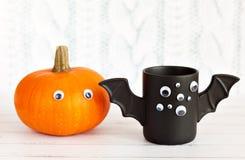 Φλιτζάνι του καφέ όπως το ρόπαλο με τα μάτια στο άσπρο υπόβαθρο αποκριών Κολοκύθα παιχνίδι Έννοια Στοκ Φωτογραφία