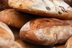 Φλοιώδεις φρέσκες χειροτεχνικές φραντζόλες ψωμιού με τις μαύρα ελιές και τα ξύλα καρυδιάς στοκ εικόνα με δικαίωμα ελεύθερης χρήσης