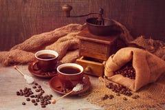 Φλυτζάνια καφέ και εκλεκτής ποιότητας μύλος με sackcloth πέρα από το ξύλινο υπόβαθρο Στοκ Εικόνα